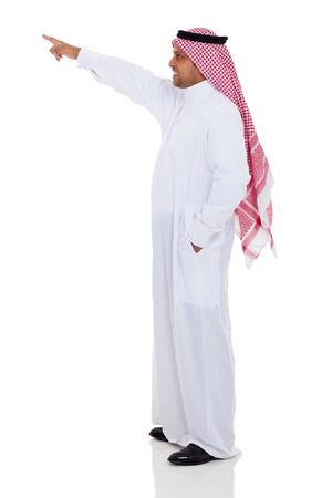 hombre arabe: Vista lateral del hombre árabe que apunta hacia arriba, aislado en blanco Foto de archivo
