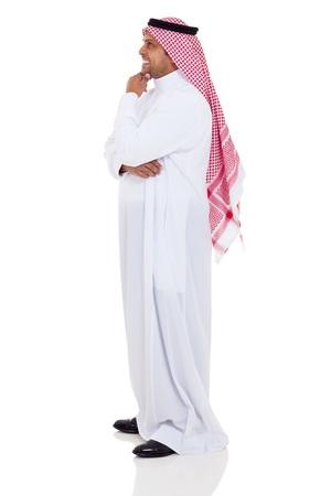 hombre arabe: Vista lateral del hombre sonriente islámico en el fondo blanco Foto de archivo
