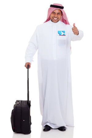 cheerful arabian businessman with luggage giving thumb up photo