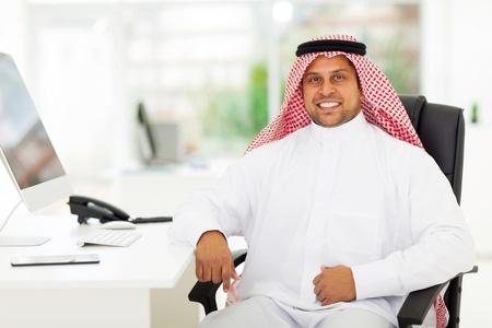 smiling arabian business man in office photo