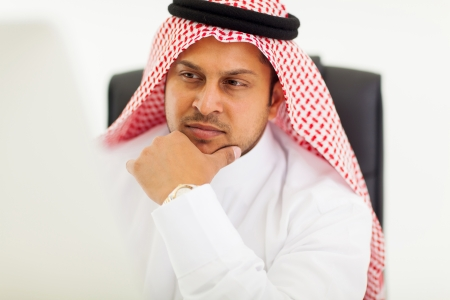 thoughtful arabic businessman looking at computer screen Stock Photo - 19637489