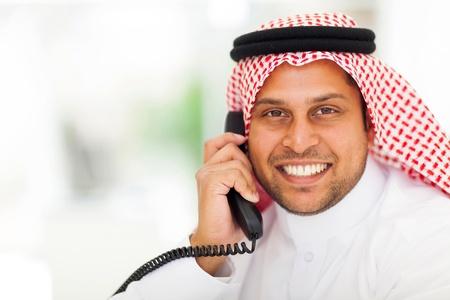 smiling middle eastern man answering telephone in office Stock Photo - 19637463