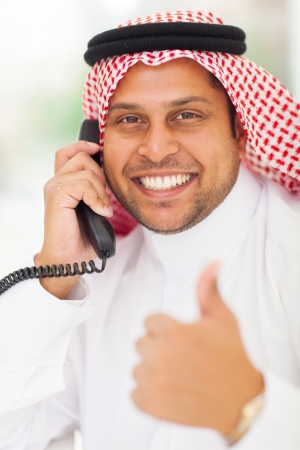 arabic businessman talking on landline phone and giving thumb up Stock Photo - 19637513