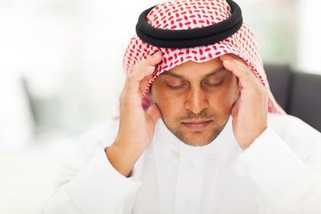 hombre arabe: el hombre árabe tiene dolor de cabeza en el trabajo