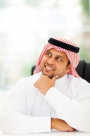 cheerful arabian businessman daydreaming in office photo