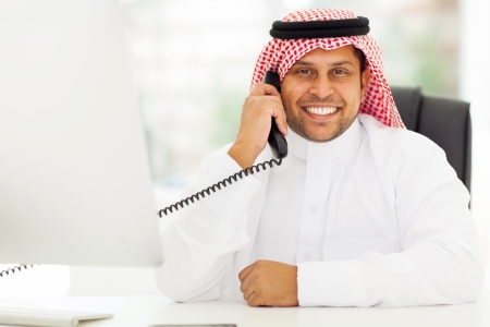 happy male arab corporate worker talking on the landline phone photo