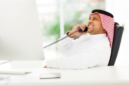 cheerful arabian corporate worker talking on the landline phone Stock Photo - 19637449