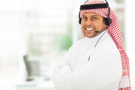 arab adult: friendly male arabian IT support worker with headphone