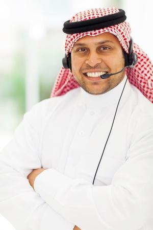 hombre arabe: sonriendo operador de call center árabe cerca retrato Foto de archivo