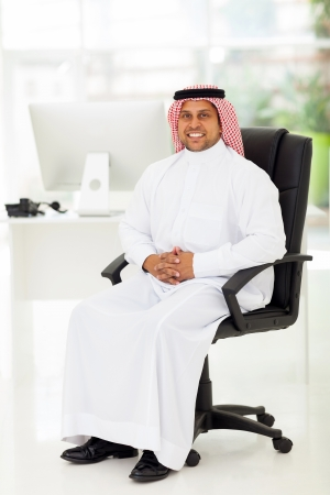 smiling middle eastern businessman sitting in modern office Stock Photo - 19637416