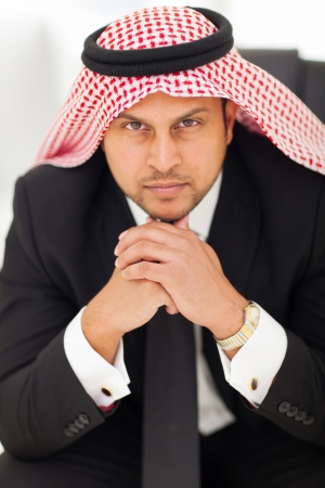 close up portrait of handsome arabian businessman sitting in office photo