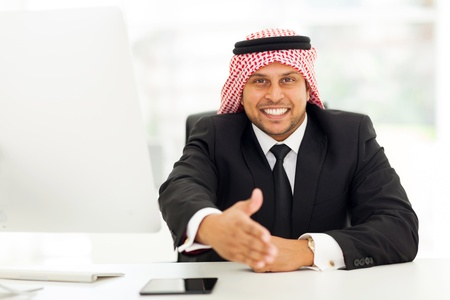 friendly arabic businessman giving handshake gesture photo
