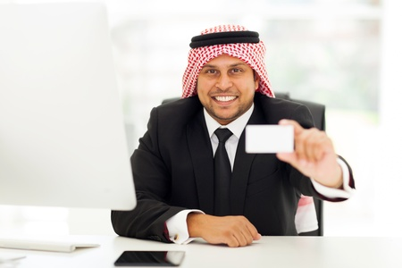 happy arabian businessman handing his business card photo