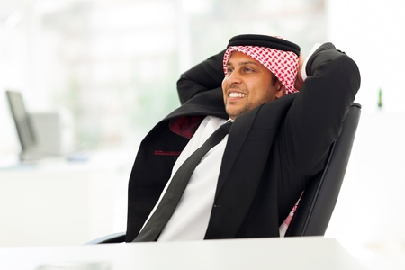 happy arab businessman relaxing in his office photo