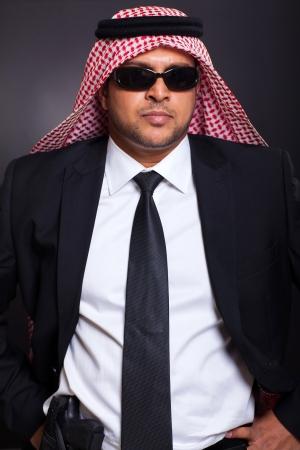 agal: islamic bodyguard with a gun against black ground Stock Photo