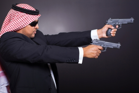 dangerous arabian hit man shooting with two guns over black background photo