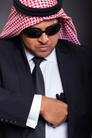 dangerous middle eastern hitman drawing his handgun on black background photo