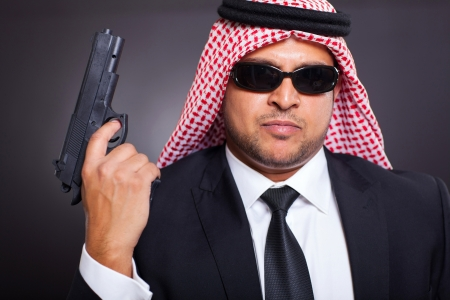 arab hit man holding gun on black background photo