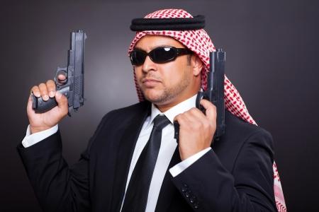 sicario: joven de Oriente Medio hitman posando con armas de fuego sobre fondo negro Foto de archivo