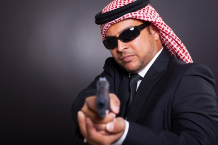 arabian spy in sunglasses holding gun on black background photo
