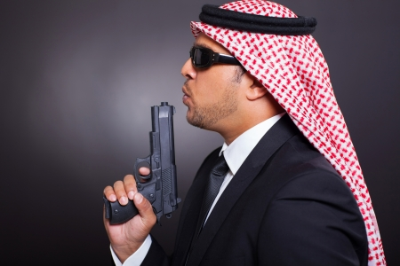 man holding gun: side view of arabian bodyguard with pistol