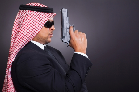 arabic secret detective holding a gun over black background photo
