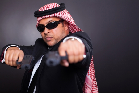 middle eastern bodyguard posing with guns on black background Stock Photo - 19637515