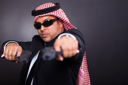 sicario: Oriente Medio guardaespaldas posando con armas de fuego sobre fondo negro
