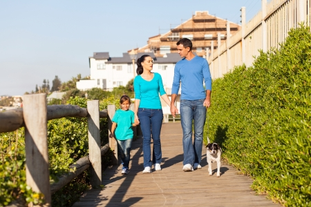 beautiful modern family walking their dog at the beach photo