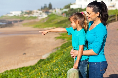 daughter pointing at ocean with mother at the beach in the morning photo