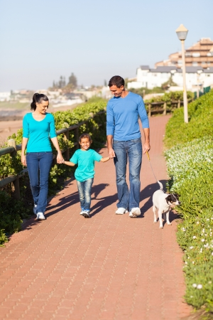 beautiful young couple with their daughter walking pet dog by seaside photo