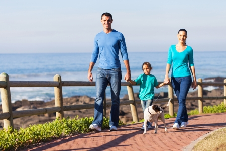 family walking: young family walking their dog at the beach