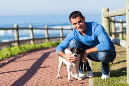man dog: cheerful young man with his pet dog at the beach