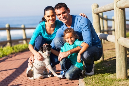 portrait of lovely family and pet dog outdoors at beach photo