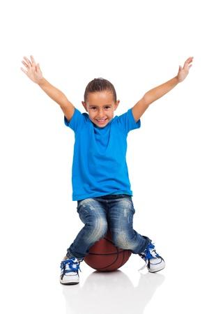 baloncesto chica: niña feliz sentado en una pelota de baloncesto sobre fondo blanco Foto de archivo