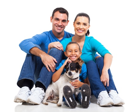 portrait of cute family sitting on floor with their pet dog isolated on white