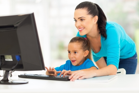 happy young mother teaching daughter computer at home photo