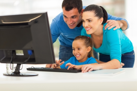 computer learning: happy modern family using computer together at home