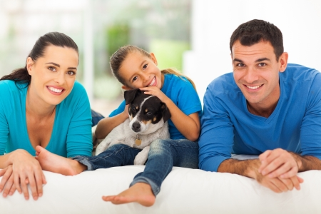 small dog: loving young family lying on bed at home with their pet dog Stock Photo