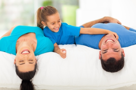 cute little girl tickling her father while family lying on bed at home photo
