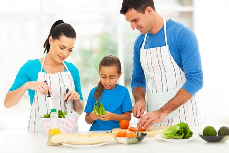 kitchen apron: lovely young family preparing food in kitchen at home Stock Photo