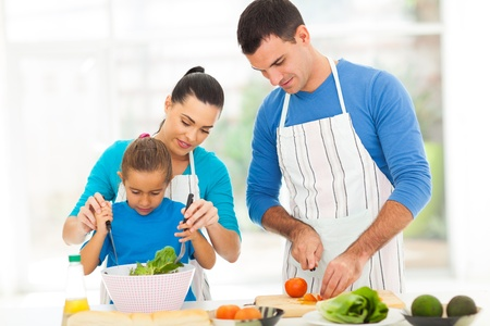 modern love: mother teaching little daughter mixing salad when family cooking in kitchen