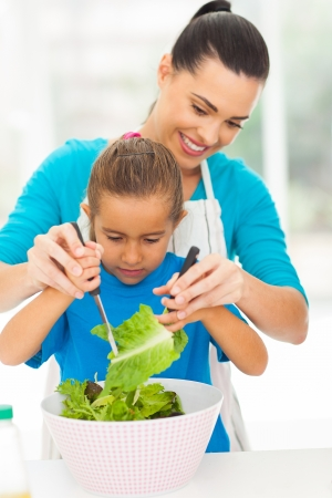 modern parents: loving mother teaching little daughter mixing salad at home