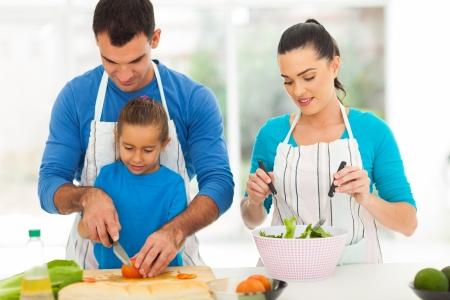 teaching adult: caring father teaching little daughter cutting vegetables while family cooking at home