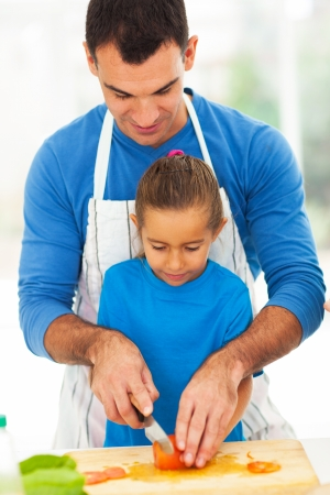 father teaching daughter: loving father teaching little daughter cooking in kitchen Stock Photo