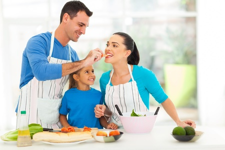 children cooking: loving husband feeding wife a piece of tomato while cooking with daughter