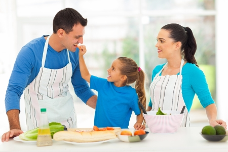apron: cute little daughter feeding father a piece of tomato in kitchen
