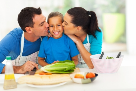 loving parents kissing little daughter in kitchen  photo