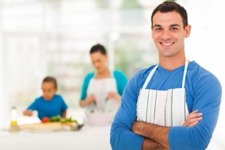 delantal: apuesto hombre de familia de pie delante de la familia en la cocina Foto de archivo