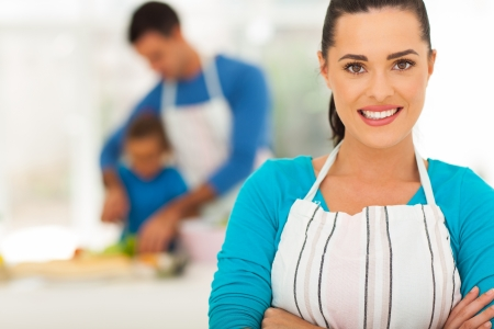 modern parents: pretty young mother in front of family in kitchen